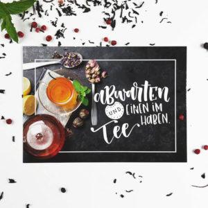 """Postkarte mit der Aufschrift """"Abwarten und einen im Tee haben."""", sowie Teetasse, Teekanne und Kräutern auf weißem Hintergrund. Designt von Mint & Limes."""