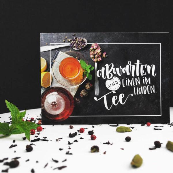 """Postkarte mit der Aufschrift """"Abwarten und einen im Tee haben."""", sowie Teetasse, Teekanne und Kräutern vor schwarzem Hintergrund auf weißem Tisch."""