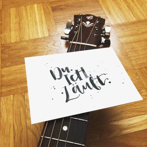 """Postkarte aus Recycling Papier mit der Aufschrift """"Du. Ich. Läuft."""" zwischen Gitarrensaiten geklemmt mit Parkettboden im Hintergrund."""