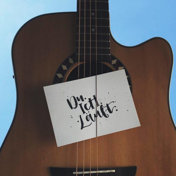 """Postkarte aus Recycling Papier mit der Aufschrift """"Du. Ich. Läuft."""" zwischen Gitarrensaiten geklemmt mit blauem Himmel im Hintergrund."""