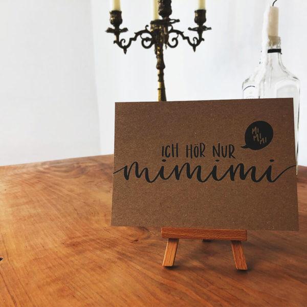 """Postkarte aus Kraftkarton mit schwarzer Aufschrift """"Ich hör nur mimimi"""" auf kleinem Holzaufsteller vor einem Kerzenhalter und einer leeren Gin Flasche."""