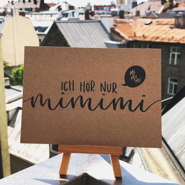 """Postkarte aus Kraftkarton mit schwarzer Aufschrift """"Ich hör nur mimimi"""" auf kleinem Holzaufsteller in der Sonne mit Hausdächern im Hintergrund. Designt von Mint & Limes."""