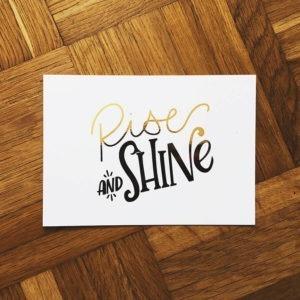 """Postkarte mit der goldenen Aufschrift """"Rise and shine"""" auf Parkettboden fotografiert."""