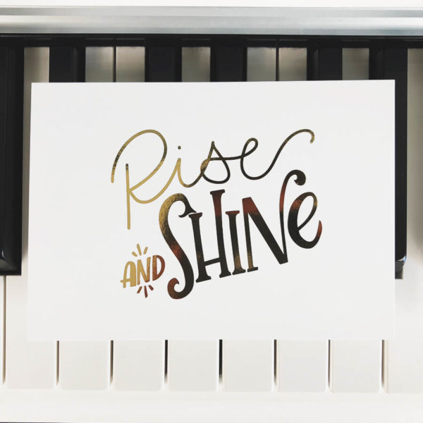 """Postkarte mit der goldenen Aufschrift """"Rise and shine"""" auf Klaviertasten liegend. Designt von Mint & Limes."""