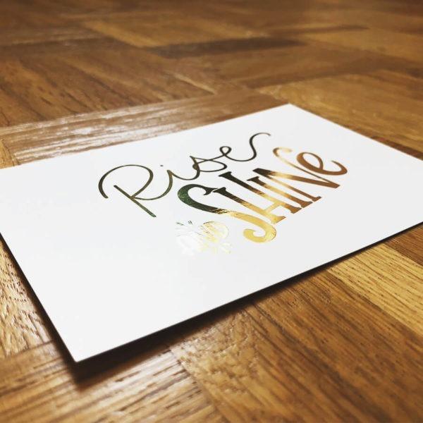"""Postkarte mit der goldenen Aufschrift """"Rise and shine"""" auf Parkettboden von der Seite fotografiert."""
