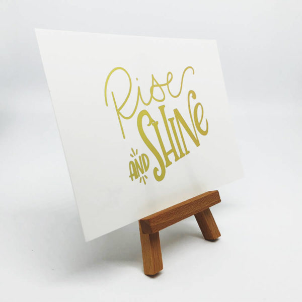 """Postkarte mit der goldenen Aufschrift """"Rise and shine"""" auf kleinem Aussteller von der Seite vor weißem Hintergrund."""