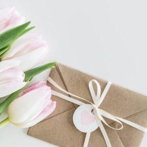Kraftpapierumschlag mit weißem Band und Herzanhänger neben weißen Tulpen.