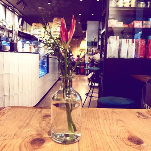 Blumenvase auf einem Tisch mit stilvoll eingerichtetem Cafe im Hintergrund