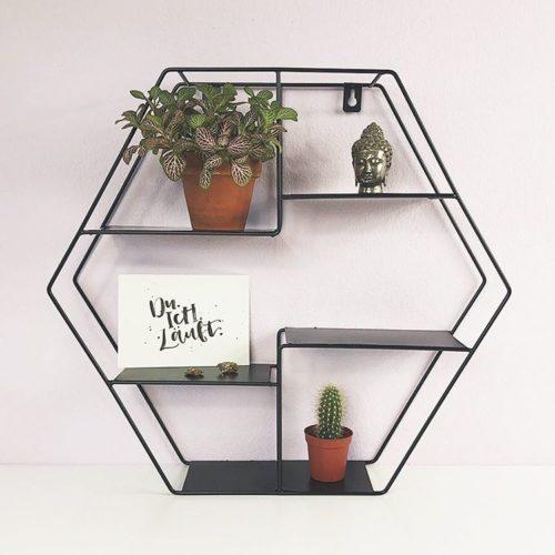 """Hexagon Wandregal aus Metall, dekoriert mit einer Zimmerpflanze, einem Buddha Kopf, einer Postkarte mit Aufschrift """"Du. Ich. Läuft."""" und einem kleinen Kaktus."""