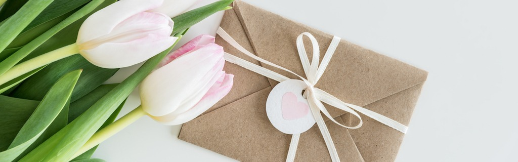 Kraftpapierumschlag mit weißem Band und Herzanhänger neben weißen Tulpen