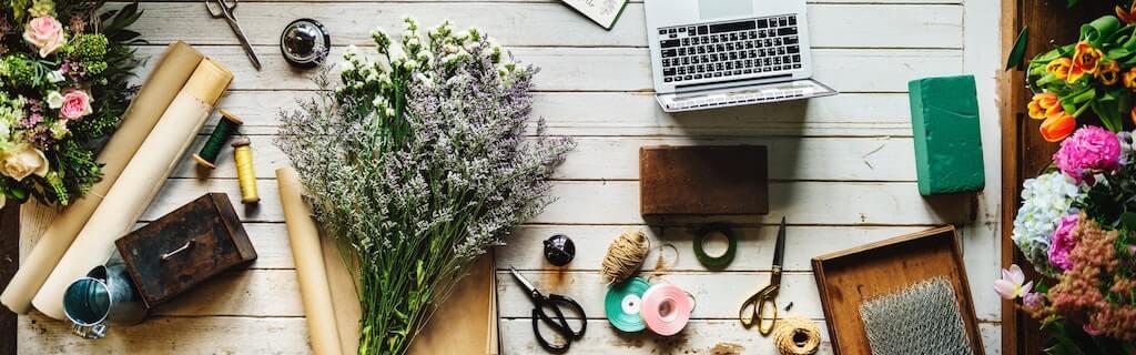 Tisch mit Laptop, Scheren, Bänder, Blumen und Verpackungsmaterial