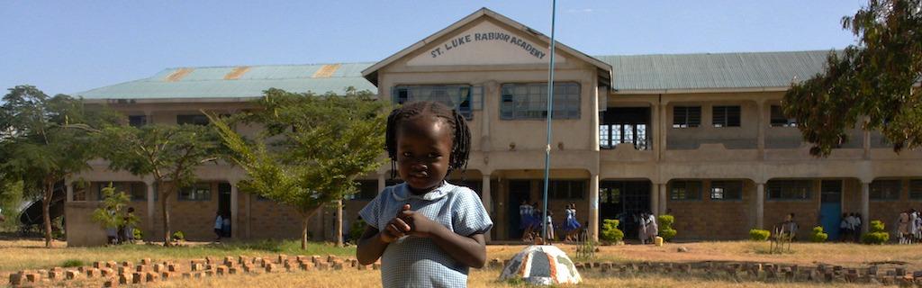 Schüchternes kenianisches Kindergartenkind vor der Schule in der Sonne
