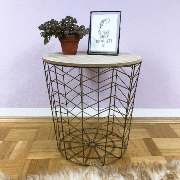 Goldener Beistelltisch aus Metall mit Holzdeckel auf dem eine Blume und ein Bilderrahmen steht.