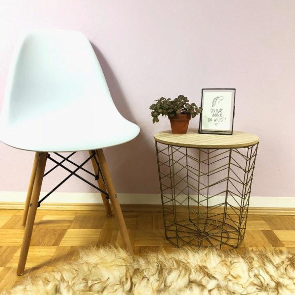 Goldener Beistelltisch aus Metall mit Holzdeckel auf dem eine Blume und ein Bilderrahmen steht. Daneben steht ein moderner weißer Stuhl vor einem Schafsfell.