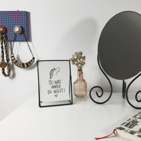"""Schwarzer Metall-Bilderrahmen zum Aufstellen mit Postkarte """"Sei was immer du willst"""". Auf Tisch neben einem Spiegel, Blumen und Buch fotografiert."""