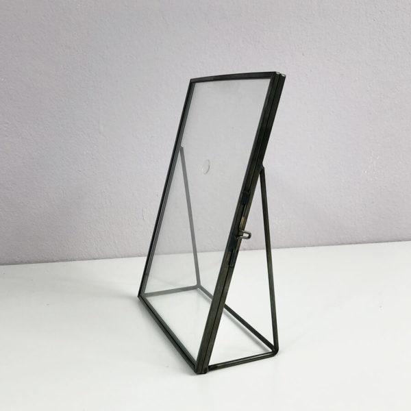 Schwarzer Metall-Bilderrahmen zum Aufstellen. Leicht seitlich fotografiert.