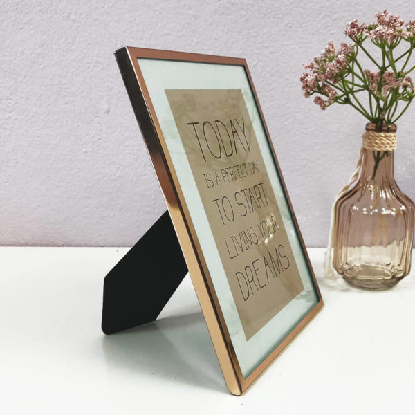 "Rose goldener Bilderrahmen mit Bild ""Today is a perfect day to start living your dreams"" seitlich neben einer Blumenvase."