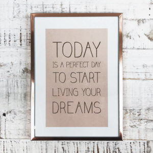 "Rose goldener Bilderrahmen mit Bild ""Today is a perfect day to start living your dreams"" von oben auf einem Holzbrett fotografiert."