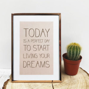 "Rose goldener Bilderrahmen mit Bild ""Today is a perfect day to start living your dreams"" frontal neben einem Kaktus."