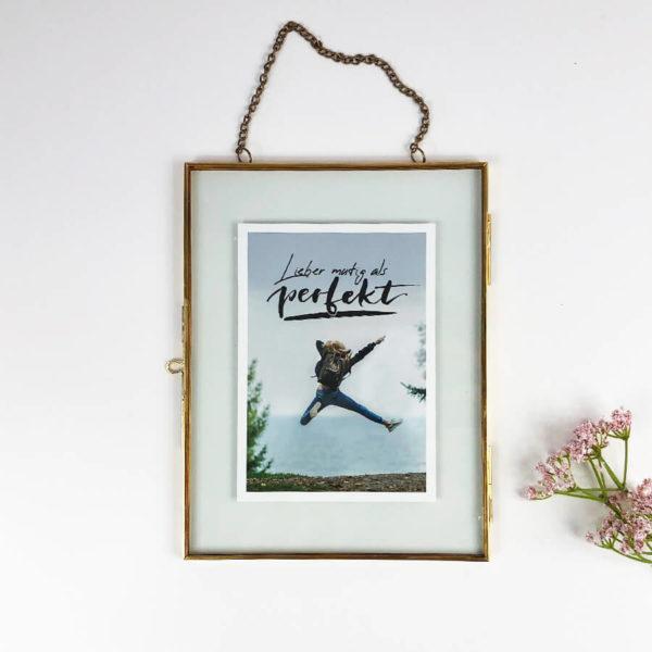 """Bilderrahmen zum Hängen in vintage Optik gold mit Postkarte """"Lieber mutig als perfekt. Von oben vor weißem Hintergrund."""