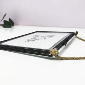 """Bilderrahmen in vintage Optik aus Metall und Glas. Schwarzer Rahmen mit Postkarte """"Du. Ich. Läuft"""" seitlich in Nahaufnahme."""