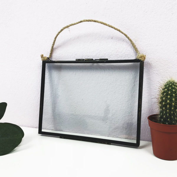 Bilderrahmen in vintage Optik aus Metall und Glas und schwarzem Rahmen, neben einem Kaktus.