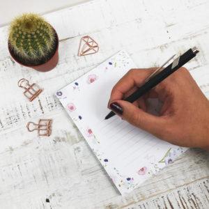 Frauenhand mit Stift, die auf einen Notizblock mit Blumenmuster schreibt. Das Bild hat einen hellen Hintergrund und ist mit Kaktus und rosé goldenen Paper Clips dekoriert.