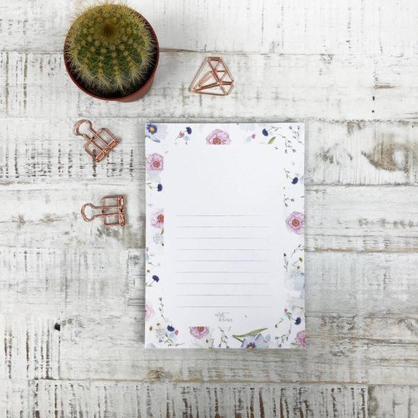 Notizblock mit Blumenmuster auf hellem Hintergrund. Dekoriert mit Kaktus und rosé goldenen Paper Clips.