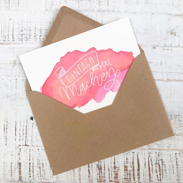 """Briefumschlag aus Kraftpapier mit Karte """"Einfach mal machen"""" vor hellem Hintergrund."""