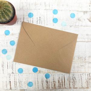 Briefumschlag aus Kraftpapier auf hellem Hintergrund und mit blauen Konfetti, sowie einem Kaktus als Dekoration.