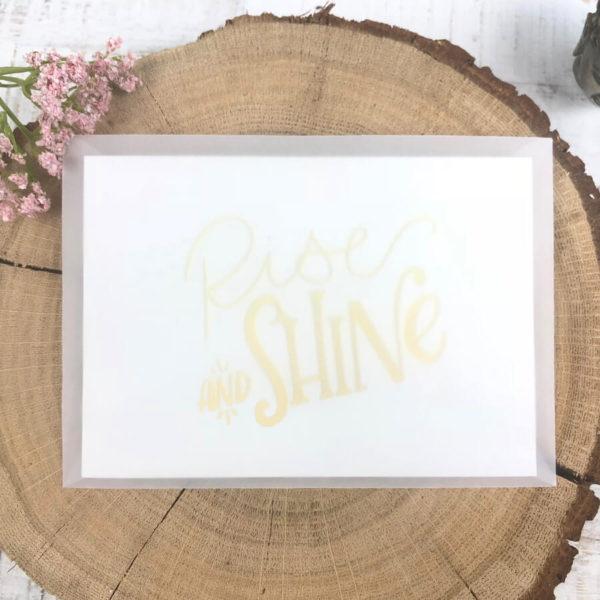 """Halb transparenter Briefumschlag mit Karte """"Rise and shine"""" auf einem aufgeschnittenen Baumstumpf neben einer Blume."""
