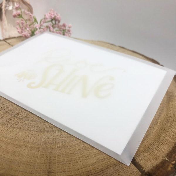 """Halb transparenter Briefumschlag mit Karte """"Rise and shine"""" auf einem aufgeschnittenen Baumstumpf neben einer Blume. Von der Seite aufgenommen."""