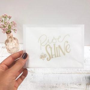 """Frauenhände mit Nagellack halten einen halb transparenter Briefumschlag mit Karte """"Rise and shine"""" vor einem hellen Hintergrund."""