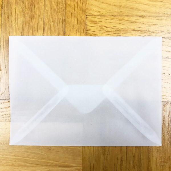 Halb transparenter Briefumschlag in Nahaufnahme auf Parkettboden.