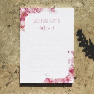 """Notizblock mit pinkem Blumenmuster und Aufschrift """"Cause every Story is different"""" auf Mamor."""