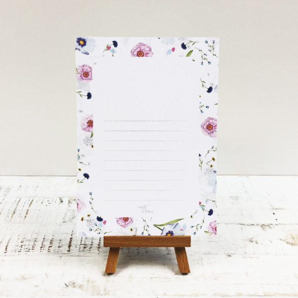 Notizblock mit hellem Blumenmuster vor weißem Hintergrund. Designt von Mint & Limes.