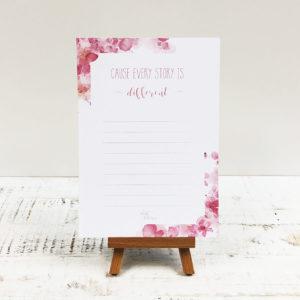 """Notizblock mit pinkem Blumenmuster und Aufschrift """"Cause every Story is different"""" vor weißem Hintergrund. Designt von Mint & Limes."""