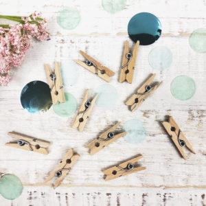 Zehn Zwicker aus Holz auf hellem Hintergrund, dekoriert mit grünem Konfetti und einer Blume.
