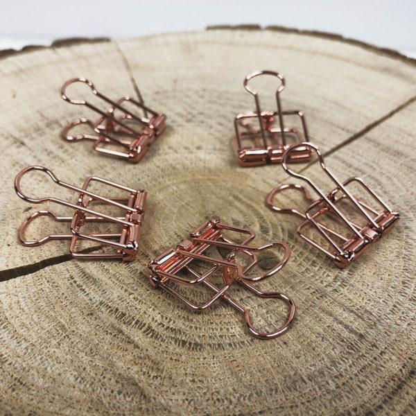 Fünf rosé goldene Papierklammern aus Metall auf einem aufgeschnittenen Baumstamm.