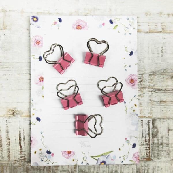 Fünf rosane Papierklammer in Herzform auf einem Notizblock mit Blumenmuster.