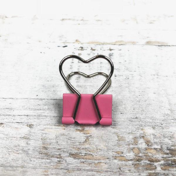 Eine rosane Papierklammer in Herzform auf weißem Hintergrund.