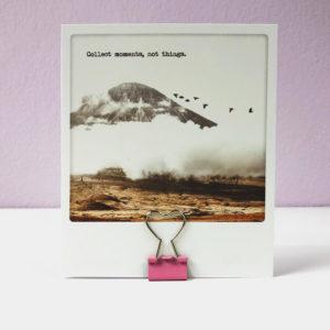 """Eine rosane Papierklammer in Herzform die eine Postkarte mit der Aufschrift """"Collect moments, not things"""" hält."""