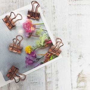Fünf rosé goldene Paper Clips die auf einer Karte mit Blumenmuster liegen.