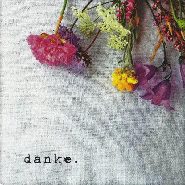 """Nahaufnahme der Polaroid Karte mit Aufschrift """"Danke."""" und Blumen."""