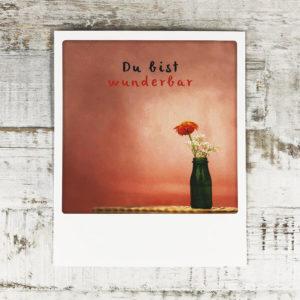 """Polaroid Karte mit Aufschrift """"Du bist wunderbar"""" und Blumenvase auf einem Tisch vor einer roten Wand."""