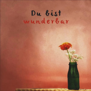 """Nahaufnahme der Polaroid Karte mit Aufschrift """"Du bist wunderbar"""" und Blumenvase auf einem Tisch vor einer roten Wand."""
