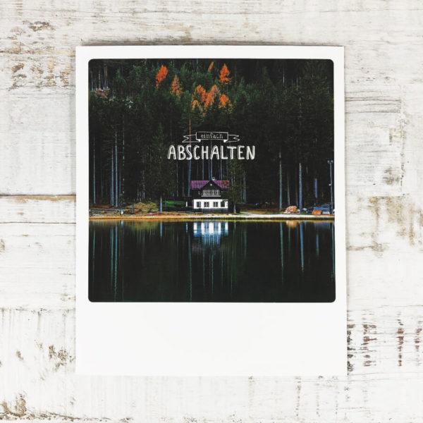 """Polaroid Karte mit Aufschrift """"Einfach abschalten"""" und idyllischem Haus am See mit Wald im Hintergrund."""
