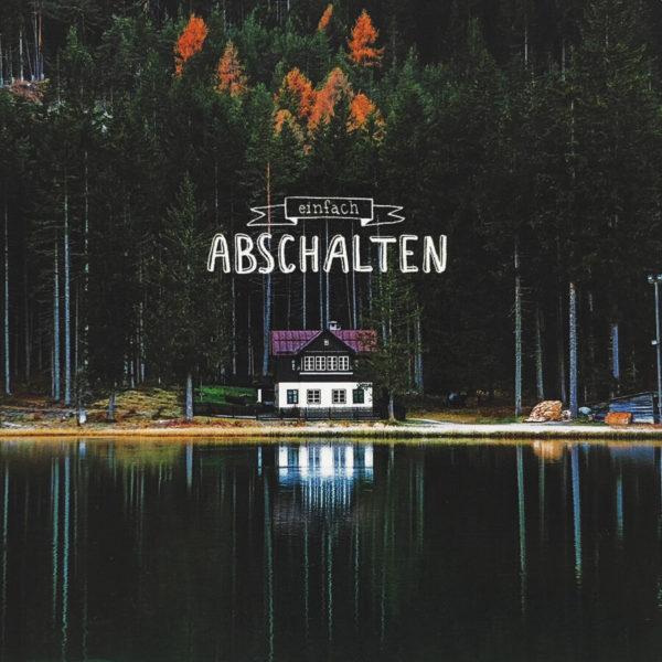 """Nahaufnahme der Polaroid Karte mit Aufschrift """"Einfach abschalten"""" und idyllischem Haus am See mit Wald im Hintergrund."""