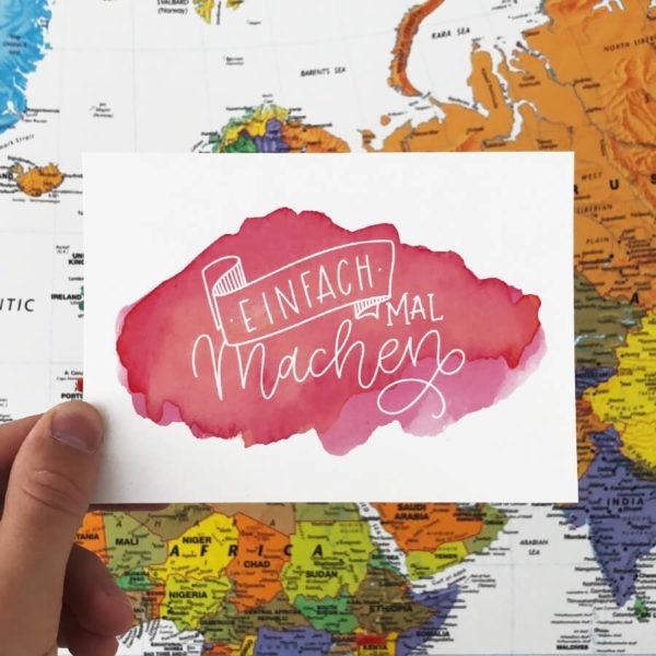 """Postkarte mit Aufschrift """"Einfach mal machen"""" vor einer Weltkarte fotografiert. Designt von Mint & Limes."""