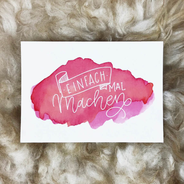 """Postkarte mit Aufschrift """"Einfach mal machen"""" von oben auf einem Schaffell fotografiert."""